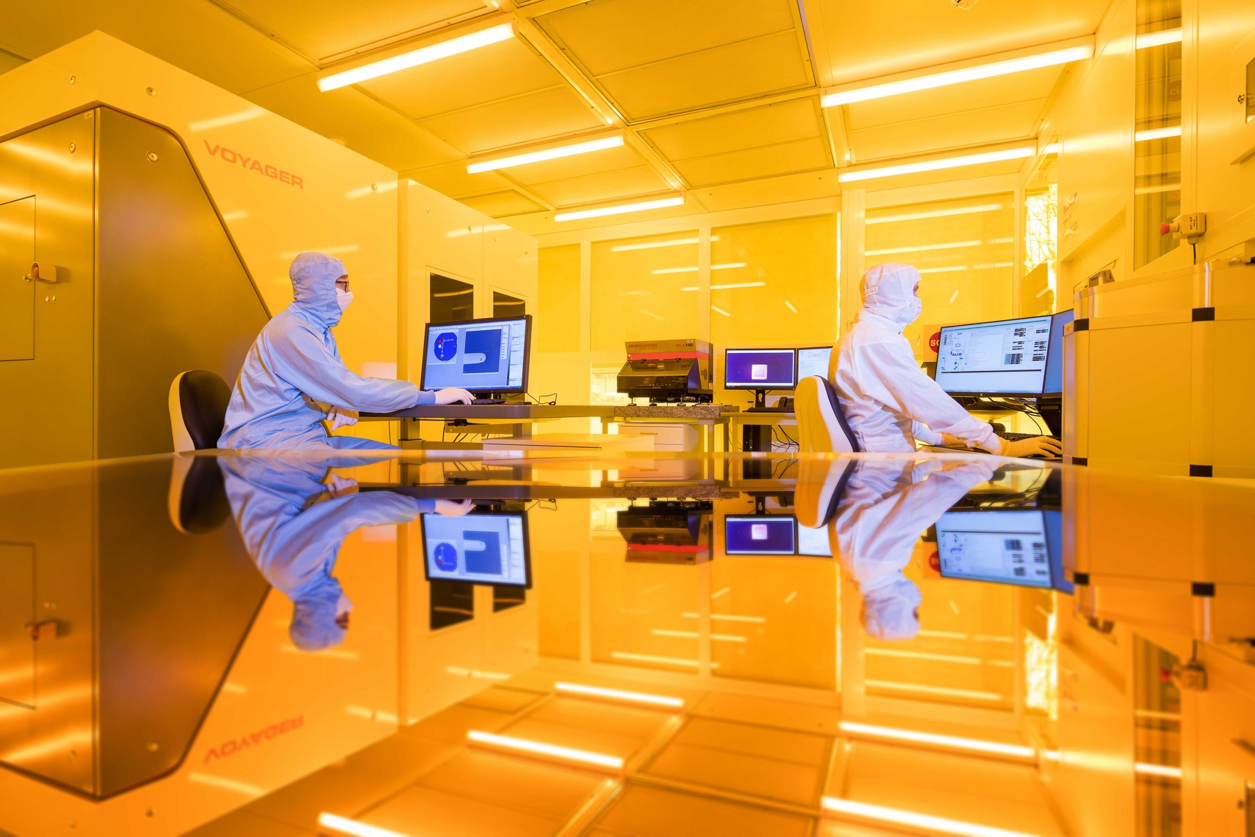 two scientists working in yellow light of the clean room