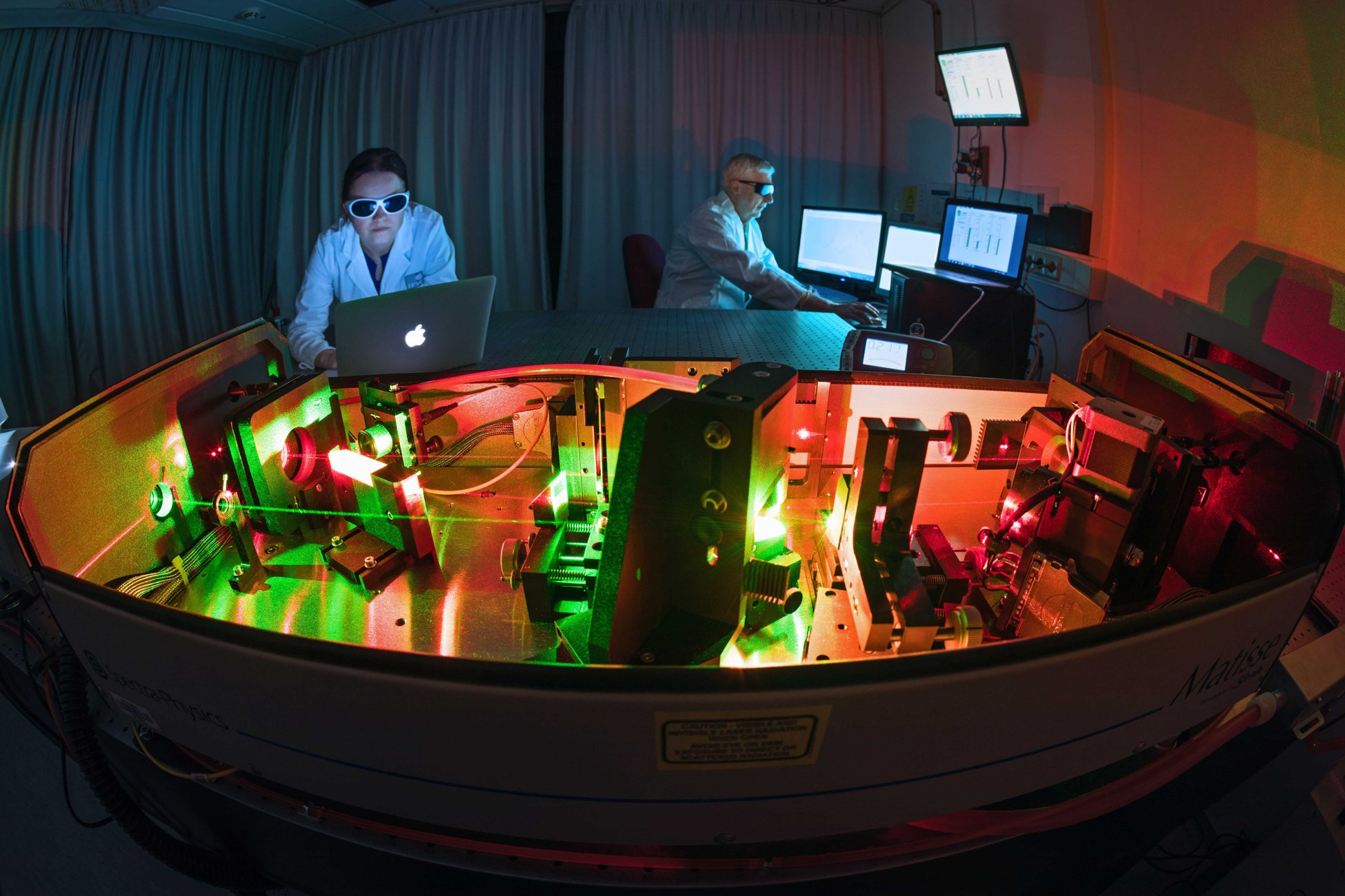 Laser laboratory with coloured laser light in dark surroundings